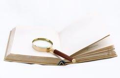Libro con la lente d'ingrandimento Fotografia Stock