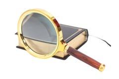Libro con la lente d'ingrandimento Fotografie Stock Libere da Diritti