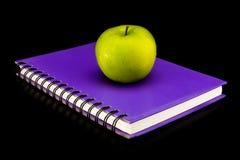 Libro con la manzana verde Fotos de archivo