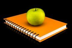 Libro con la manzana verde Imagenes de archivo