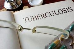 Libro con la tubercolosi e le pillole di diagnosi immagini stock