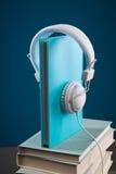 Libro con le cuffie Fotografie Stock