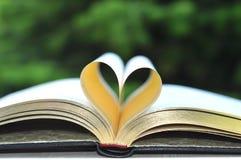 Libro con le Pagine Gialle sulla Tabella in giardino con il cuore della forma delle pagine Fotografie Stock Libere da Diritti