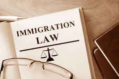 Libro con legge di immigrazione di parole immagini stock