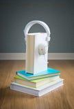 Libro con los auriculares blancos Imágenes de archivo libres de regalías