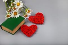 Libro con los poemas románticos, las flores y dos corazones foto de archivo libre de regalías
