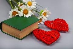 Libro con los poemas románticos, las flores y dos corazones imagen de archivo libre de regalías