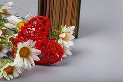 Libro con los poemas románticos, las flores y un corazón fotos de archivo libres de regalías