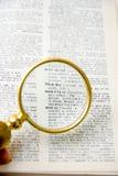 Libro con una lente de la lupa Foto de archivo libre de regalías