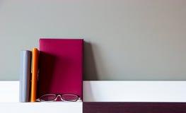 Libro, cuadernos y vidrios en estante moderno fotografía de archivo