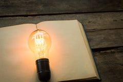 Libro d'annata e lampadina sulla tavola che di legno si accende Immagine Stock Libera da Diritti
