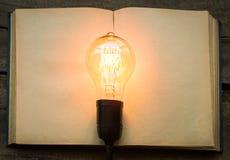 Libro d'annata e lampadina sulla tavola che di legno si accende Fotografie Stock Libere da Diritti