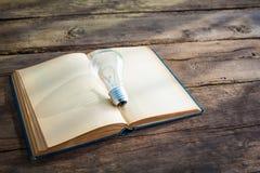 Libro d'annata e lampadina sulla tavola di legno Fotografie Stock Libere da Diritti