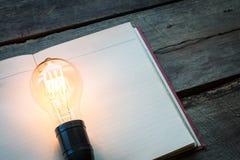 Libro d'annata e lampadina sulla tavola di legno Fotografia Stock