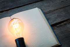 Libro d'annata e lampadina sulla tavola di legno su fondo bianco Fotografia Stock