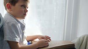 Libro de Braille en la fuente de caracteres ciega de la lectura del niño de los brazos que se sienta en alféizar metrajes