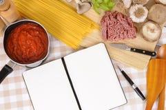 Libro de cocina con los ingredientes para los espaguetis boloñés Foto de archivo