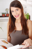 Libro de cocina de la lectura de la mujer joven en la cocina Imágenes de archivo libres de regalías