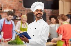 Libro de cocina indio masculino de la lectura del cocinero en la clase de cocina imagen de archivo libre de regalías