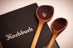Libro de cocina viejo y dos cucharas de cocinar de madera Foto de archivo