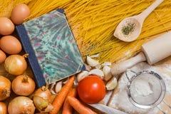 Libro de cocina y espaguetis imagen de archivo