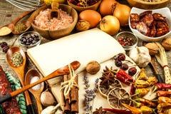 Libro de cocina y especia en una tabla de madera Preparación de alimento Un libro viejo en la cocina Recetas para la comida imagen de archivo libre de regalías