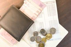 Libro de cuentas tailandés de ahorro del dinero y del banco en la tabla de madera Fotos de archivo
