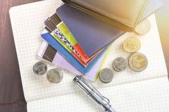 Libro de cuentas tailandés de ahorro del dinero y del banco en la tabla de madera Foto de archivo libre de regalías