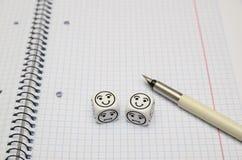Libro de ejercicio abierto con los dados del humor (felices) Foto de archivo