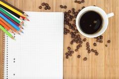 Libro de ejercicio vacío con café y lápices coloreados Fotografía de archivo libre de regalías