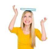 Libro de equilibrio feliz de la muchacha del estudiante en la pista Fotos de archivo libres de regalías