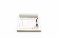 Libro de factura que abren la página en blanco con la pluma Fotografía de archivo