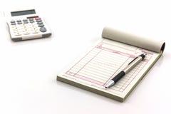 Libro de factura que abren la página en blanco con la pluma y la calculadora Imagenes de archivo