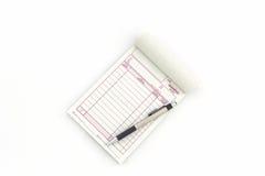 Libro de factura que abren la página en blanco con la pluma Foto de archivo libre de regalías