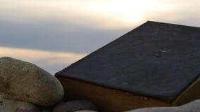 Libro de la biblia que pone en la arena con las piedras en el lapso de tiempo de la puesta del sol almacen de video