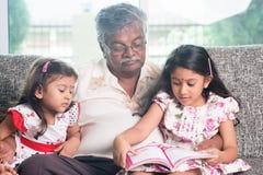 Libro de la historia de la lectura de la familia junto imágenes de archivo libres de regalías