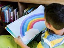 Libro de la historia de los niños de la lectura del muchacho en biblioteca fotografía de archivo libre de regalías