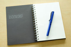 Libro de la inspiración y pluma azul fotografía de archivo