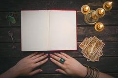 Libro de la magia y de las cartas de tarot fotos de archivo