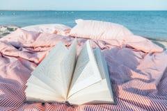 Libro de la relajación y de lectura cerca del mar Fotos de archivo libres de regalías
