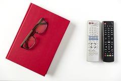Libro de la TV y vidrios teledirigidos, rojos en la mesa de centro blanca Imagen de archivo