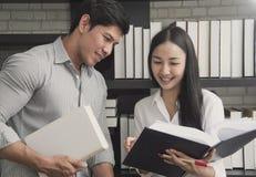 Libro de lectura adolescente asiático del estudiante en escuela de biblioteca Fotos de archivo libres de regalías