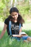 Libro de lectura adolescente de la muchacha en la naturaleza Foto de archivo libre de regalías