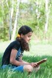 Libro de lectura adolescente de la muchacha en la naturaleza Imagen de archivo