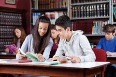 Libro de lectura adolescente de los compan@eros de clase en biblioteca Foto de archivo libre de regalías
