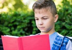 Libro de lectura adolescente del muchacho Fotografía de archivo