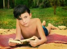 Libro de lectura adolescente del muchacho en la playa Fotos de archivo libres de regalías