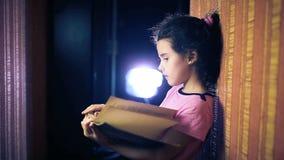 Libro de lectura adolescente del niño de la muchacha mientras que se coloca metrajes