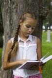 Libro de lectura adolescente joven de la muchacha cerca del árbol de pino Foto de archivo libre de regalías