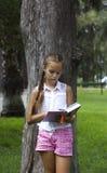 Libro de lectura adolescente joven de la muchacha cerca del árbol de pino Fotografía de archivo